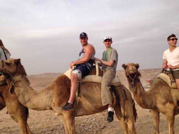 Me (center) riding a camel in the desert